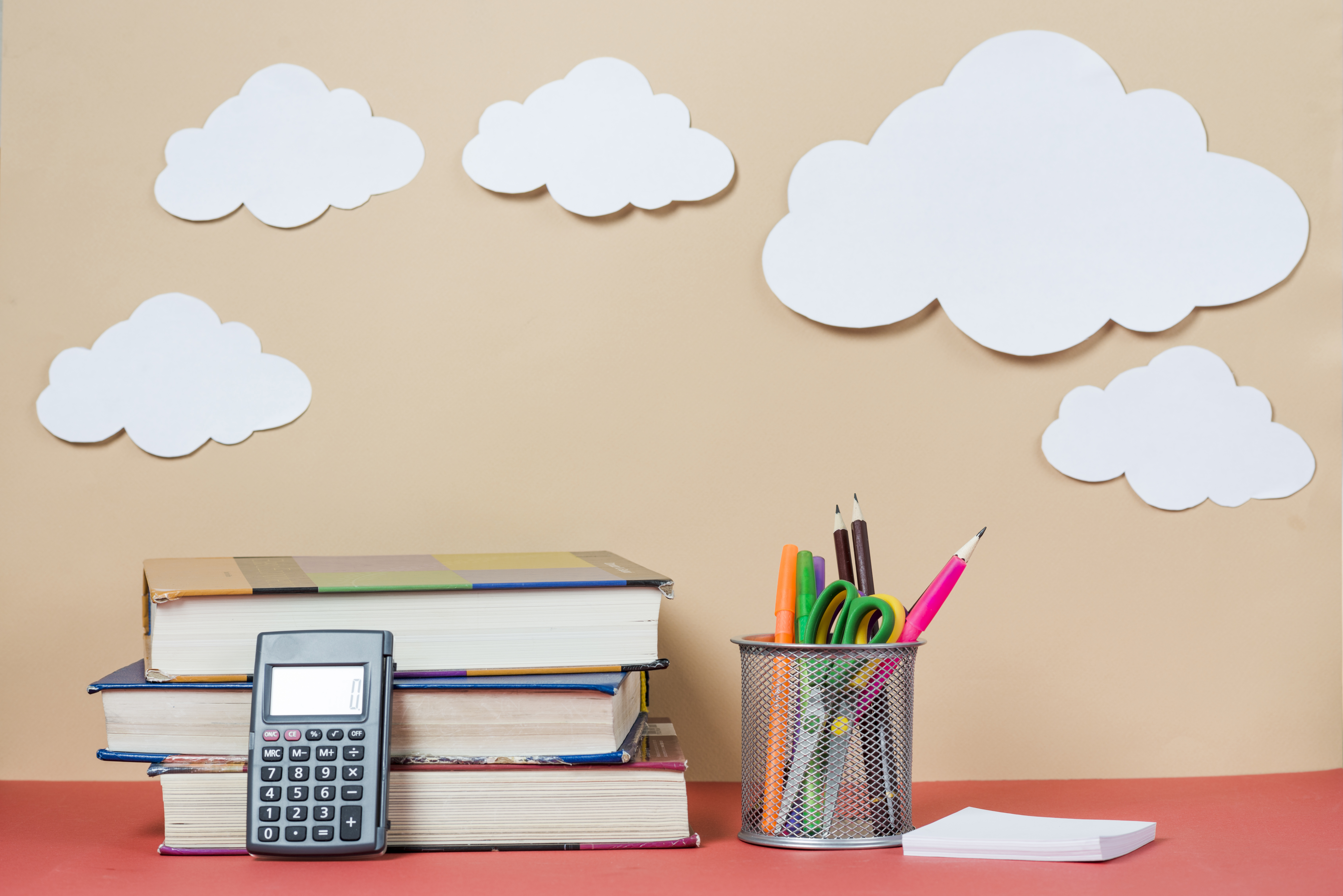 Libros y material de estudio sobre un fondo con nubes